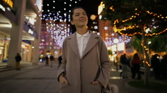 Woman walking in night city and contemplate illuminated street Stock Footage