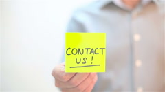 Contact Us. A man sticks a note on transparent screen Stock Footage