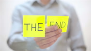 The end. A man sticks a note on transparent screen Stock Footage