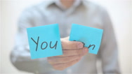 You can. A man sticks a note on transparent screen Stock Footage
