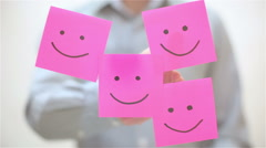 Smile. A man sticks a note on transparent screen Stock Footage
