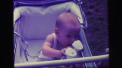1972: tender moment when baby is playing with his plush on his crib LYNBROOK Stock Footage