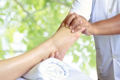 Masseur doing reflexology,Thai foot massage in spa on nature background Stock Photos