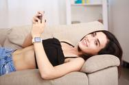Young attractive girl using her smartwatch and phone at home in the living room Stock Photos
