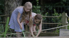 4K Little girls at conservation center exploring pond with fishing nets Stock Footage