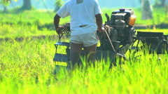 Java, Indonesia - August 2016: Asian male farmer ploughing field with motorized Stock Footage