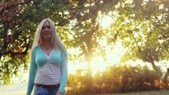 Joyful young woman with blond hair swirls in autumn Park in slow motion on Stock Footage