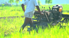 Java, Indonesia - August 2016: Asian farmer with motorized ploughing machine in Stock Footage