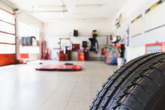 Defocused view into the auto repair shop with a tire in front Stock Photos