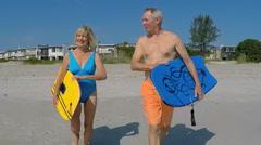 Loving fit senior Caucasian couple in swimwear walking with bodyboards  Stock Footage