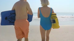 Fit healthy senior Caucasian couple in swimwear running with bodyboards Stock Footage