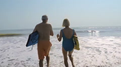 Fit healthy mature Caucasian couple in swimsuits running with bodyboards  Stock Footage