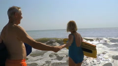 Fit active mature Caucasian man and woman in swimsuits holding body boards  Stock Footage