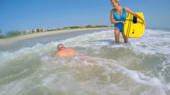 Active smiling retired Caucasian couple in swimsuits having fun with bodyboards Stock Footage