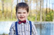 Handsome little plump boy in shirt and bow tie grimaces in sunny green park Stock Photos