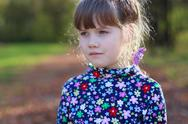 Sad little girl looks away in sunny green park, shallow dof, close up Stock Photos