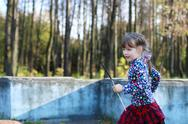 Cute little girl in red skirt runs in sunny green park with old fountain Stock Photos