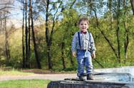 Smiling little boy with bow tie and jeans stands in sunny green park Stock Photos