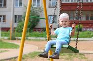 Little cute girl in hat swings on children playground at summer day Stock Photos