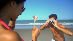 Young Caucasian man taking a picture of Latin American woman in swimwear  Stock Footage
