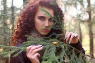 Beautiful woman looks through fir branch in forest, shallow dof Stock Photos
