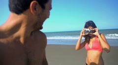 Young loving multi ethnic couple in swimsuits having fun taking a photo  Stock Footage