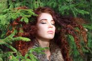 Young pretty woman with closed eyes among fir branches in forest, close up Stock Photos