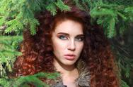 Beautiful young woman poses among fir branches in forest, shallow dof Stock Photos