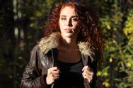 Pretty woman in jacket with sunglasses poses at sunny day in autumn forest Stock Photos