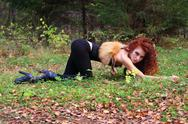 Beautiful girl with curly hair poses on grass as animal in autumn forest Stock Photos