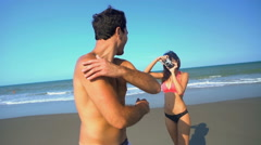 Hispanic woman taking a photo of young Caucasian American man wearing swimsuits Stock Footage