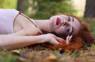 Pretty woman with red hair in jersey lies on dry foliage in autumn forest Stock Photos