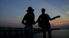 Silhouette of young carefree male and female dancing and playing the guitar Stock Footage