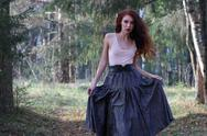 Young cute woman in skirt and belt poses on wind in sunny autumn forest Stock Photos