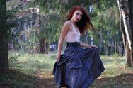 Young cute woman in skirt poses on wind in sunny autumn forest Stock Photos
