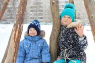 Happy girl with little brother smile during snowfall at winter outdoor Stock Photos