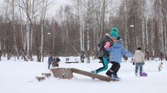 Girl helps her little brother to run on log during snowfall in winter park Stock Footage