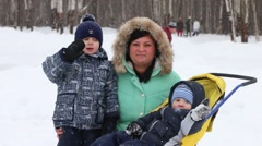 Mother and two sons wave hands, one boy kisses mother during snowfall Stock Footage