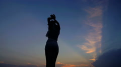 Silhouette of young attractive Latin American woman wearing hat enjoying sunset Stock Footage