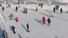 Ice skating people on ice rink at sunny winter day, above view Stock Footage