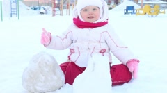 Happy little girl plays with snow on playground at winter sunny day Stock Footage