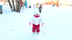 Happy little girl goes and boy plays with shovel on playground at winter Stock Footage