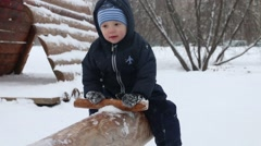Little cute boy on log seesaw during snowfall in winter park Stock Footage
