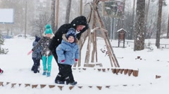 Happy mother and little son play, two children and man near they during snowf Stock Footage