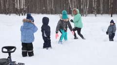 Woman and four children play snowballs during snowfall in winter park Stock Footage