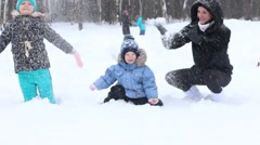 Mother, girl and little boy throw up snow during snowfall in winter park Stock Footage