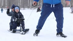 Male hand drags two happy little boys in sled near other boy during snowfall Stock Footage