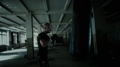 Strong athlete hits a punching bag. Medium shot. Stock Footage