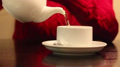 Female hands pour hot tea into white cup on table in cafe, shallow dof Stock Footage