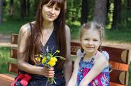 Happy mother and daughter sit with flowers on bench in park at summer, focus  Stock Photos